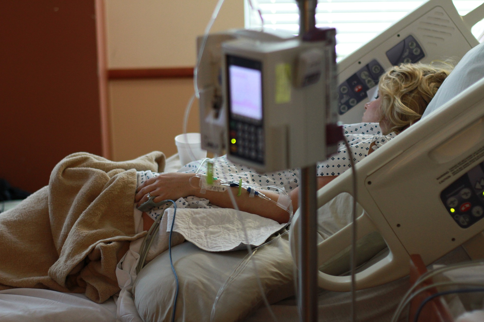 woman in a hospital bed with IV tubes and an IV pole
